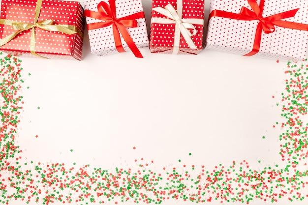 Contenitori di regalo di natale con i nastri e le scintille su bianco