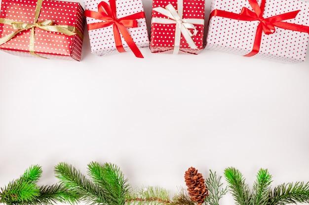 Contenitori di regalo di natale con i nastri, i rami di abete e il cono su bianco