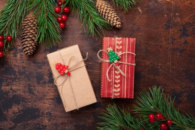 Contenitori di regalo e rami di abete su fondo di legno. biglietto di auguri di natale. vista dall'alto. copyspace