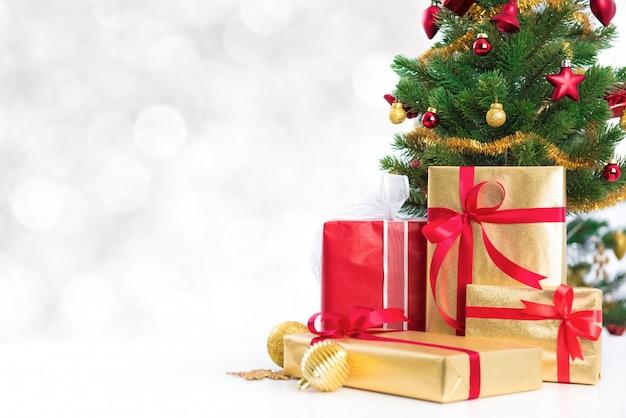 Contenitori di regalo ed albero di natale decorato colourful su bokeh bianco