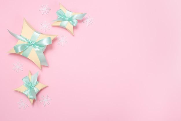 Contenitori di regalo gialli con il nastro verde chiaro e fiocchi di neve bianchi sui precedenti rosa, disposizione piana con lo spazio della copia. inverno, concetto di auguri di natale