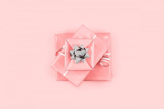 Contenitori di regalo rosa con l'arco e il nastro d'argento bianchi, vista superiore