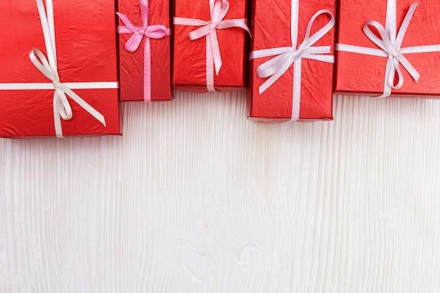 Contenitori di regalo rossi su fondo di legno bianco. copia spazio. vista dall'alto. regali per san valentino, festa della donna, anniversario o festa.