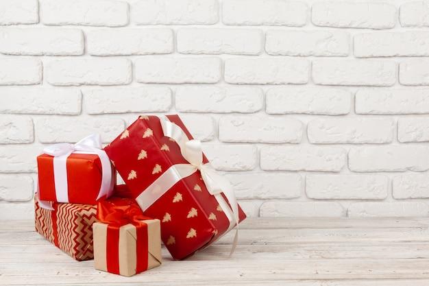 Contenitori di regalo variopinti contro il fondo bianco del muro di mattoni