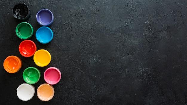 Contenitori di vernici colorate su sfondo nero strutturato