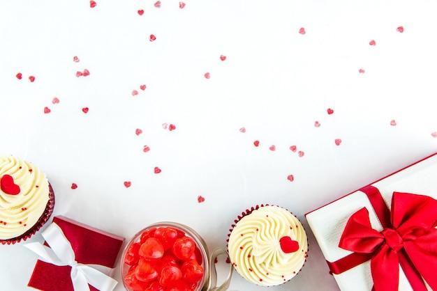 Contenitori e dolci di regalo di san valentino su libro bianco con il fondo di struttura di forma del cuore
