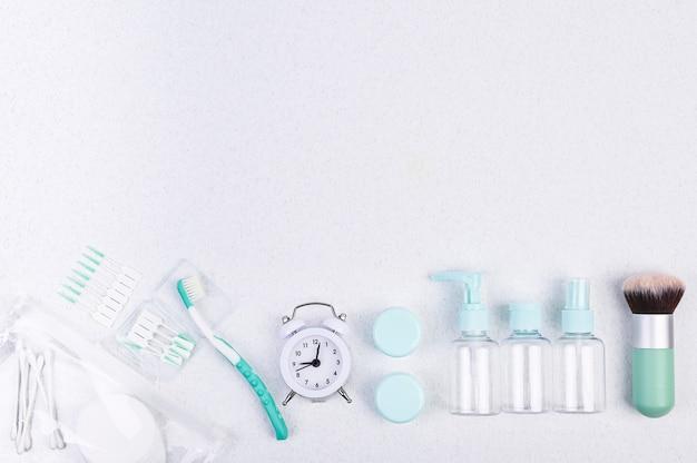 Contenitori in plastica, spazzolino da denti e sveglia per viaggiare flat lay.