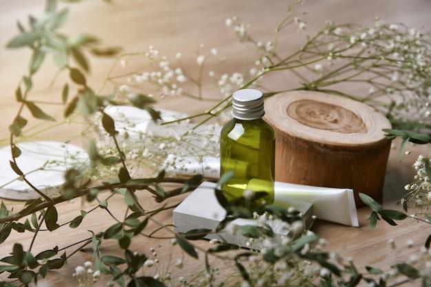 Contenitori per bottiglie cosmetici che imballano con le foglie di erbe verdi, etichetta in bianco per marcare a caldo organico, concetto di prodotto di bellezza naturale della cura della pelle.
