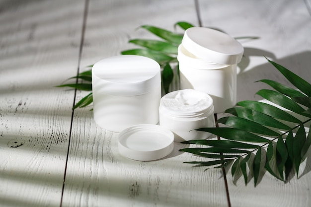 Contenitori per bottiglie cosmetici con foglie di erbe verdi