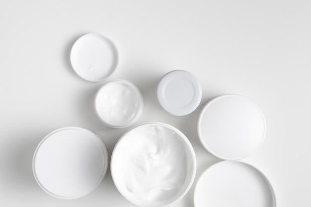Contenitori per la cura del corpo distesi su sfondo chiaro