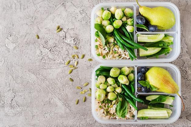 Contenitori per la preparazione di pasti verdi vegani con riso, fagiolini, bruxelles, cetrioli e frutta. cena a pranzo.