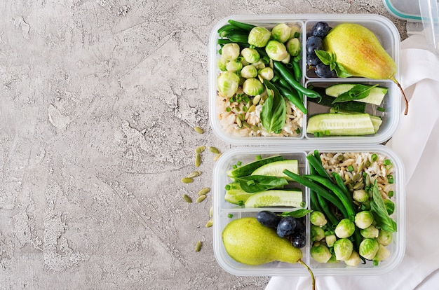 Contenitori per la preparazione di pasti verdi vegani con riso, fagiolini, cavoletti di bruxelles, cetrioli e frutta. cena a pranzo. vista dall'alto. disteso