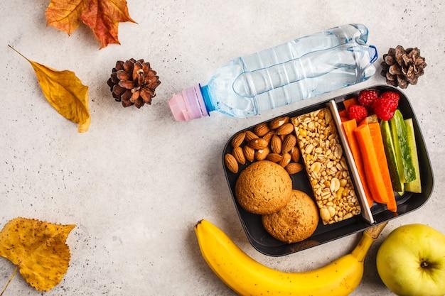 Contenitori per preparare pasti sani a scuola con barretta di cereali, frutta, verdura e snack. alimento da asporto su fondo bianco, vista superiore.