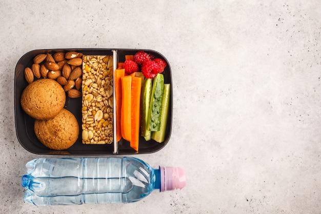 Contenitori per preparare pasti sani con barretta ai cereali, frutta, verdura e snack. alimento da asporto su fondo bianco, vista superiore.