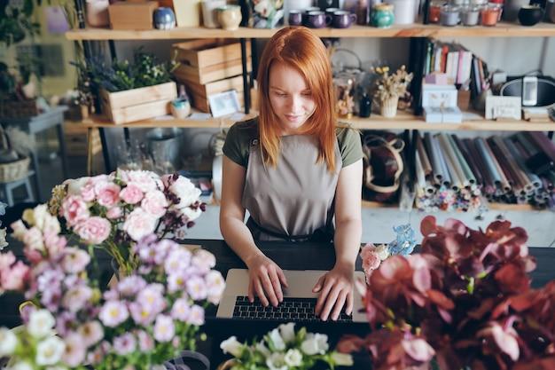 Contento fiorista piuttosto rossa in grembiule in piedi al bancone con fiori e lavora con i social media del negozio di fiori