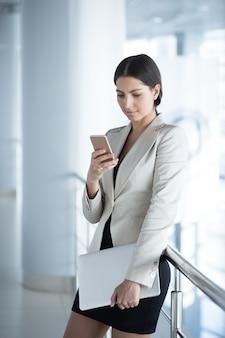 Contenuto business lady con smartphone e computer portatile