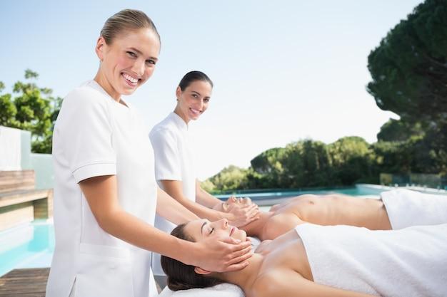 Contenuto coppia godendo testa massaggi a bordo piscina
