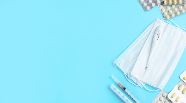 Contenuto di medetsin con compresse, siringhe, maschere per il viso, termometro su uno sfondo chiaro.
