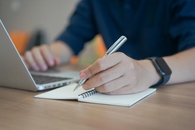 Contenuto o qualcosa di scrittura della mano dell'uomo d'affari sul taccuino con per mezzo del computer portatile a casa dell'ufficio