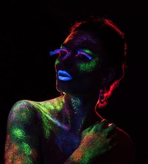 Contorno a luce rossa sulla donna sensuale con il trucco di vernice fluorescente