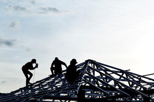 Contraente in silhouette lavorando su un tetto