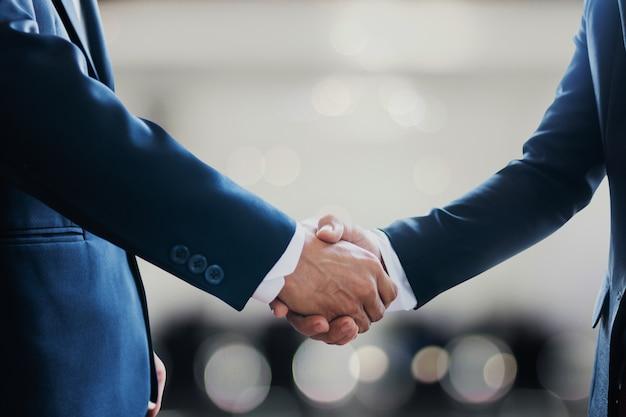 Contratto di successo negoziare e concetto di stretta di mano, due uomini d'affari si stringono la mano con il partner per celebrare la partnership, lavoro di squadra, affare nella riunione della stanza dopo comunicazione di successo, accordo