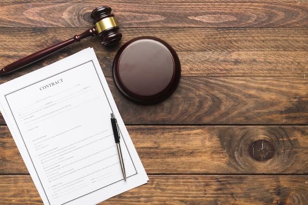 Contratto disteso e martelletto del giudice sulla tavola di legno