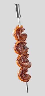Controfiletto arrosto allo spiedo su sfondo bianco. picanha barbecue.