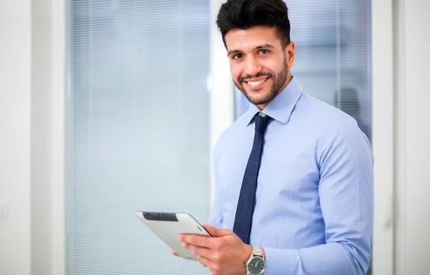 Controllando la sua posta giovane uomo d'affari bello che utilizza il suo touchpad mentre stando nell'ufficio.