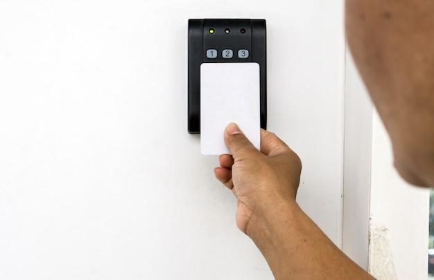 Controllo accessi alla porta - giovane donna che tiene una chiave magnetica per bloccare e sbloccare la porta., keycard