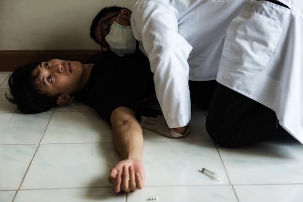 Controllo del battito cardiaco di un uomo morto in overdose