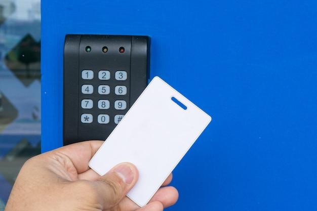 Controllo di accesso della porta - giovane donna che tiene una carta chiave per bloccare e sbloccare porta