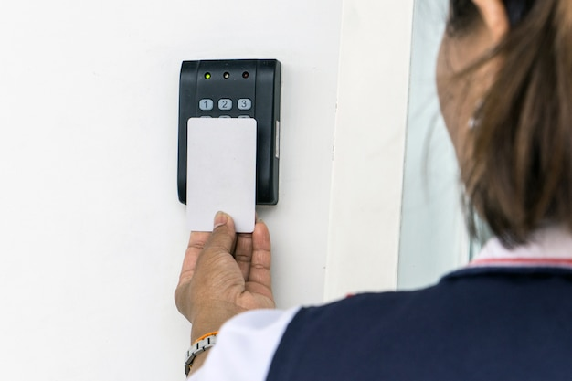 Controllo di accesso della porta - giovane donna che tiene una carta chiave per bloccare e sbloccare porta.