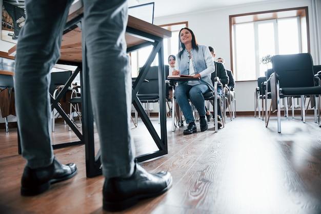 Conversazione attiva con la folla. gruppo di persone alla conferenza di lavoro in aula moderna durante il giorno