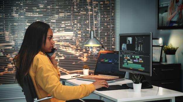 Conversazione femminile con il capo dallo smartphone e lavoro con il metraggio