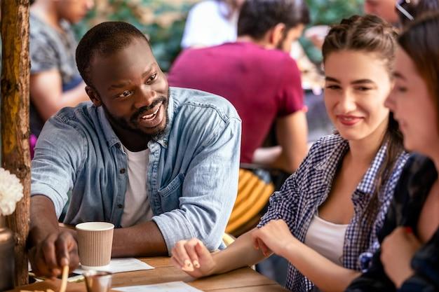 Conversazione informale con i migliori amici in un accogliente ristorante in una calda giornata estiva