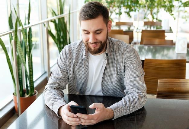 Conversazione telefonica. ritratto di uomo intelligente barba sorridente in ufficio moderno con smartphone, messaggistica sms su richiesta, controllo e-mail, navigazione internet web. free lance attraenti dell'uomo d'affari in caffè