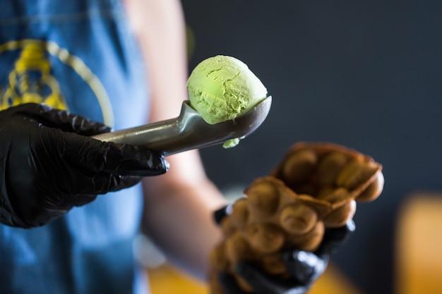 Cook prepara i waffle di hong kong con gelato, marmellata e frutta. giovane donna che tiene i wafer di bolla di hong kong