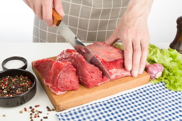 Cook taglia carne cruda su una tavola di legno