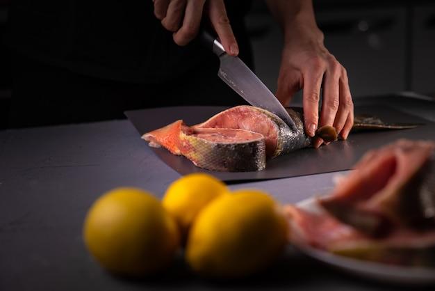 Cook taglia il pesce a pezzi con un coltello su una tavola grigia