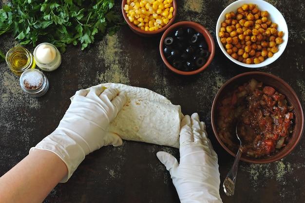 Cooking shaanma vegan. le mani nei guanti da cucina impongono un ripieno di pane pita per preparare lo shawarma. cucina mediorientale.