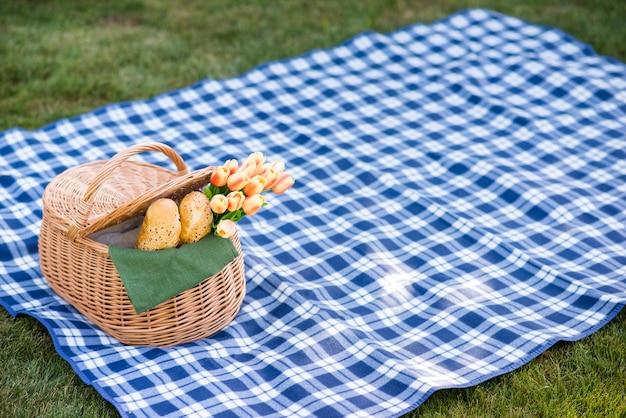 Coperta da picnic con un cesto sull'erba