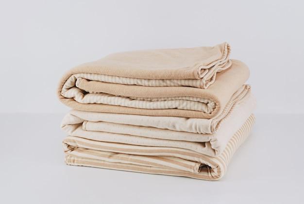 Coperta di cotone beige naturale piegata avvolta mucchio del primo piano su bianco