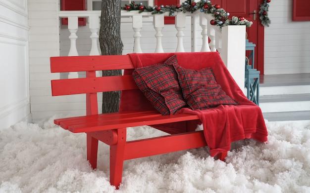 Coperta rossa e cuscini sul banco rosso con neve artificiale bianca all'aperto