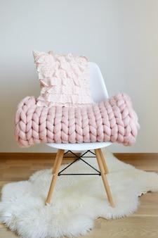 Coperta scozzese rosa gigante in lana lavorata a maglia su sedia in legno bianco sedia stile scandinavo