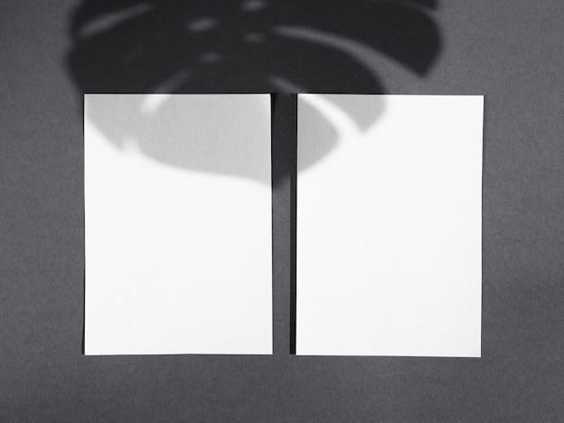 Coperte bianche su uno sfondo grigio scuro con un'ombra di foglia di ficus