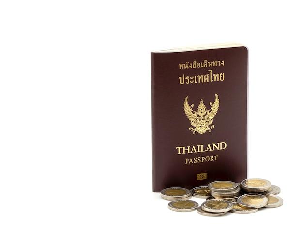 Copertura del passaporto della tailandia, cittadino di identificazione con le monete isolate su fondo bianco.
