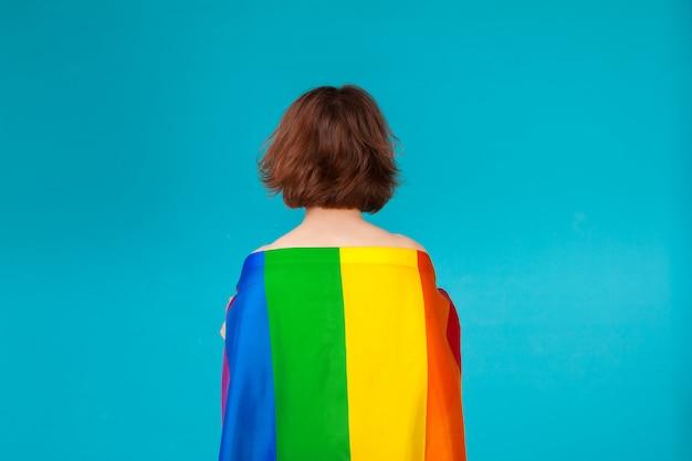 Copertura della giovane donna con la bandiera di orgoglio di lgbt