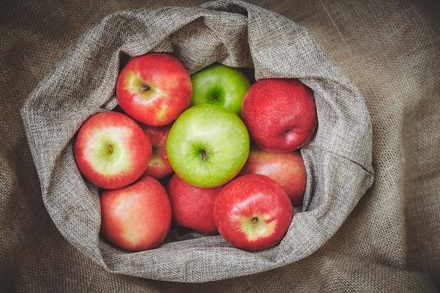 Copertura organica della merce nel carrello delle mele con tela di sacco su struttura del fondo