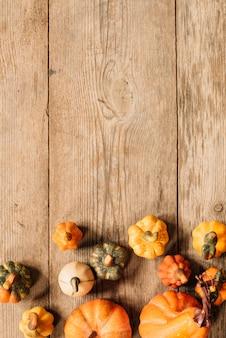 Copi la composizione nello spazio con gli elementi di autunno su fondo di legno